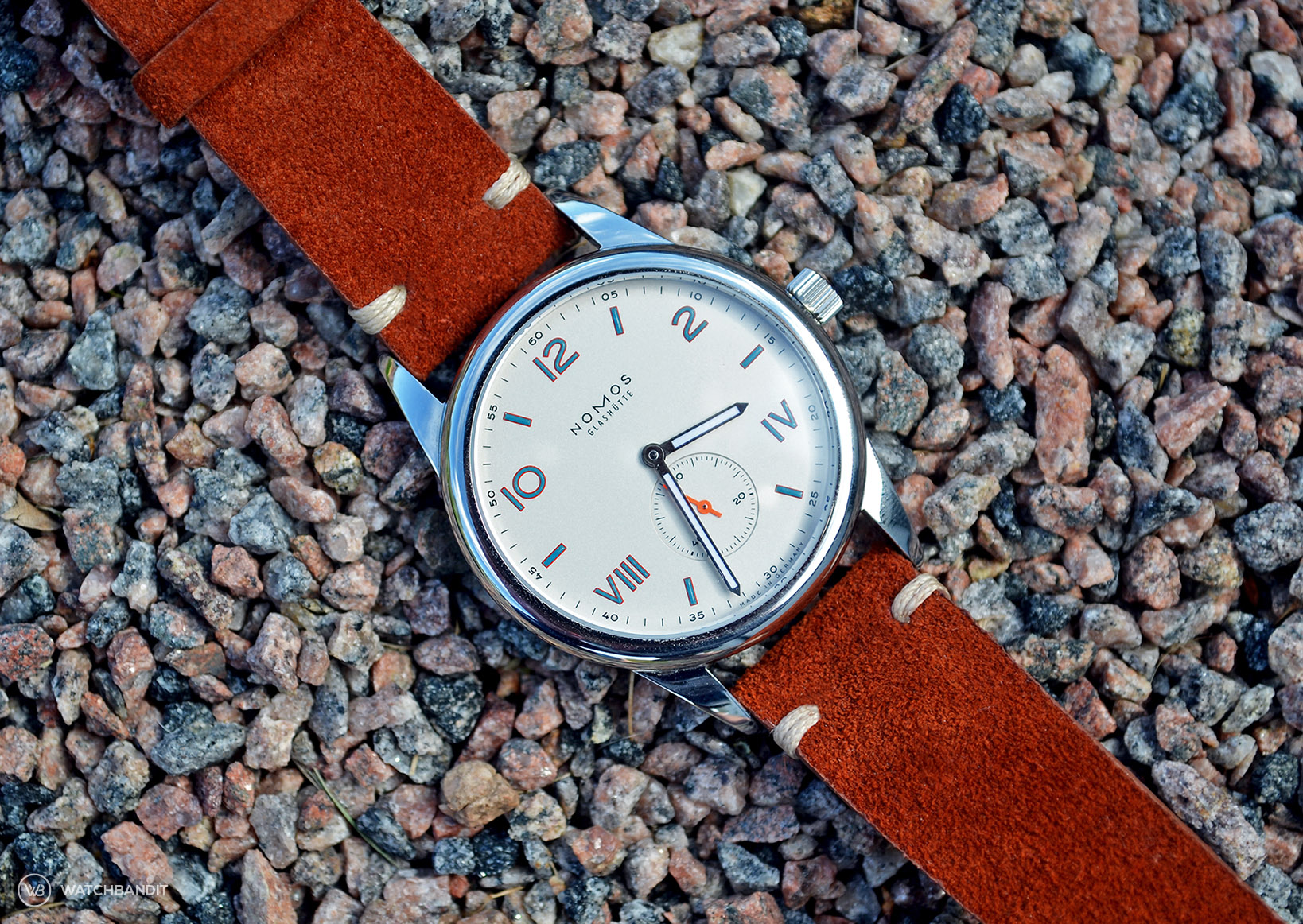 NOMOS Club Campus with rusty brown suede strap lying on stones by WB Original