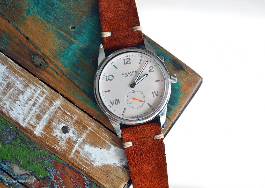 NOMOS Club Campus with rusty brown suede strap lying on colored table by WB Original